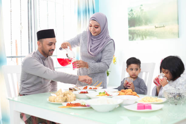 a malay muslim family having hari raya aidlfitri/ eid-ul-fitr meals - ketupat stock pictures, royalty-free photos & images