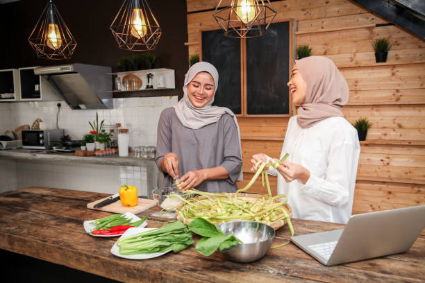 malay muslim young female adults cooking in the kitchen - ketupat stock pictures, royalty-free photos & images
