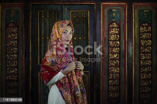 A young Malay Muslim woman pose inside a traditional Malay house, donning batik sarong over her head.