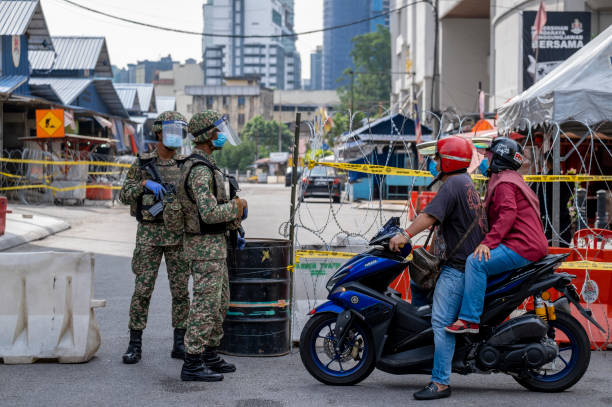 Malaysia Coronavirus disease 2019 (COVID-19) outbreak Kuala Lumpur, Malaysia - May 06, 2020: Malaysian army guard the entrance to wet market in Chow Kit after 16 new coronavirus infections were detected. Coronavirus disease 2019 (COVID-19) outbreak. migrant worker stock pictures, royalty-free photos & images