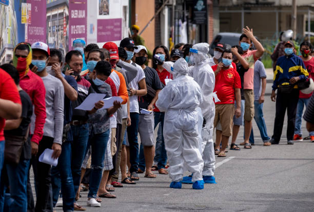 Malaysia Coronavirus disease 2019 (COVID-19) outbreak Kuala Lumpur, Malaysia - May 06, 2020: Foreign migrant workers lining up before do the COVID-19 screening test. Coronavirus disease 2019 (COVID-19) outbreak. migrant worker stock pictures, royalty-free photos & images
