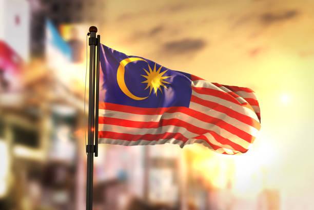 Malaysia Flag Against City Blurred Background At Sunrise Backlight stock photo