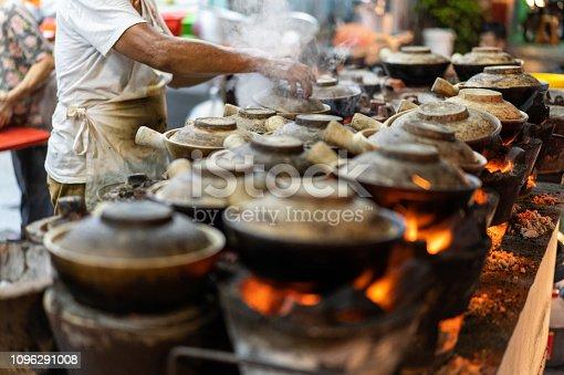 Malaysia Street Hawker cooking Clay pot Chicken Rice in night market at Kuala Lumpur.