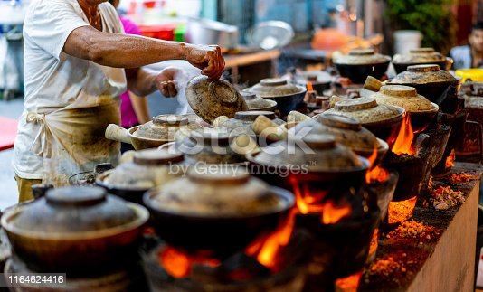 Malaysia Street Hawker cooking Clay pot Chicken Rice in night market at Kuala Lumpur.