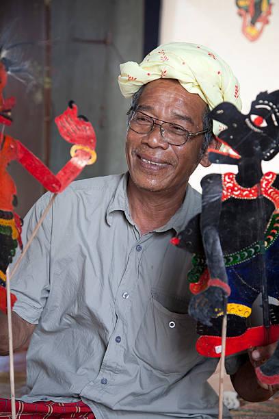 malaysia, making shadow puppet, wayang kulit. - wayang kulit stock photos and pictures