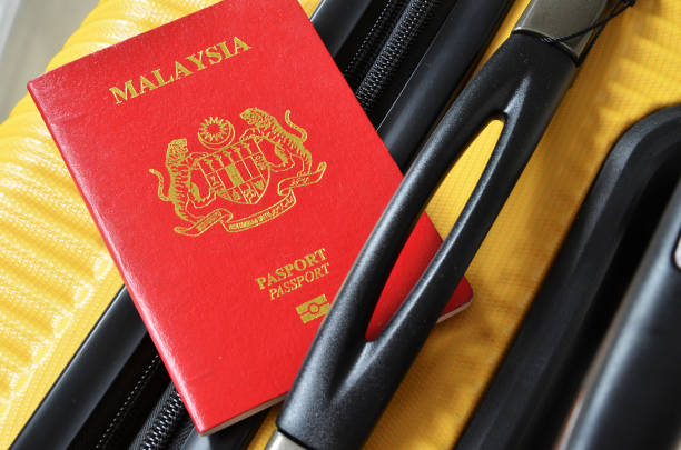 Malaysia passport on a yellow suitcase Malaysia passport on a yellow suitcase. Travel concept pasport malaysia stock pictures, royalty-free photos & images