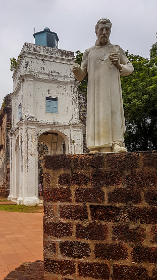 St. Francis Xavier Statue in Malacca placed on a brick wall. The figure doesn't have a palm. In the back is famous Famosa, Portugal settlement.