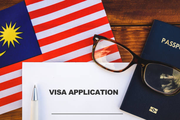 Malaysia visa application Flag of Malaysia , visa application form and passport on table pasport malaysia stock pictures, royalty-free photos & images