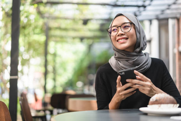 Malaysian ambitious businesswoman with smartphone in her hand. Muslim Malaysian woman during lunch break using her smartphone in Kuala Lumpur, Malaysia. indonesian ethnicity stock pictures, royalty-free photos & images