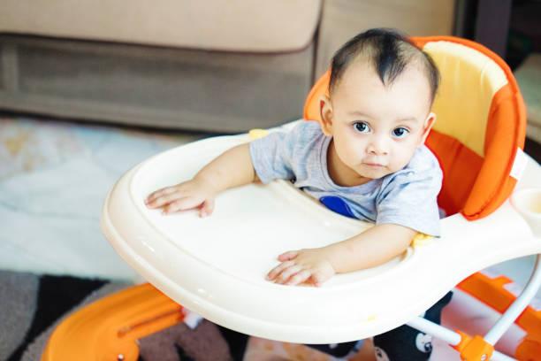 Malaysian bossy baby boy serious portrait in walker stock photo