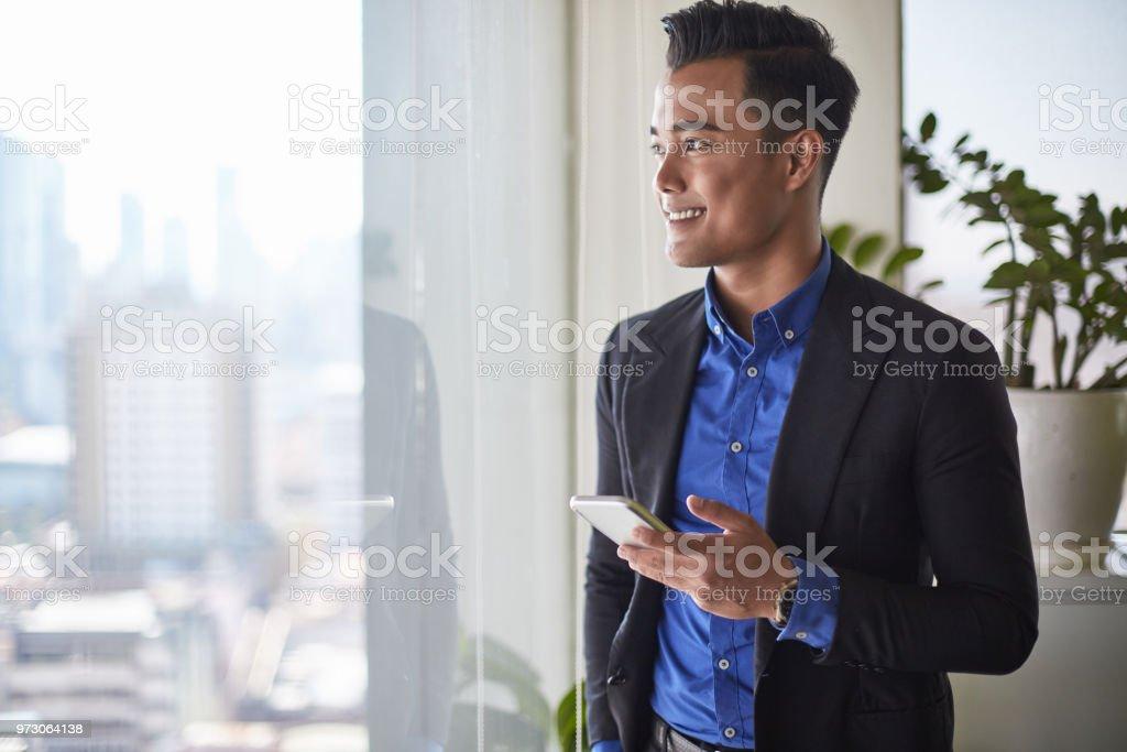 Malaysische Geschäftsmann auf Fenster mit Handy im Büro – Foto
