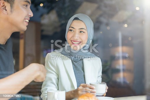 As seen through a window, a smiling young Malaysian businesswoman sits inside a coffee shop with her husband.  She listens to him talk as she raised her coffee mug.