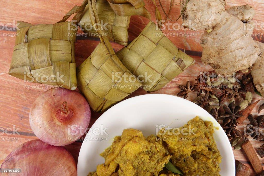 Malaysian dish Rendang Ayam or dry curry chicken and Ketupat Nasi (Rice Dumpling). stock photo