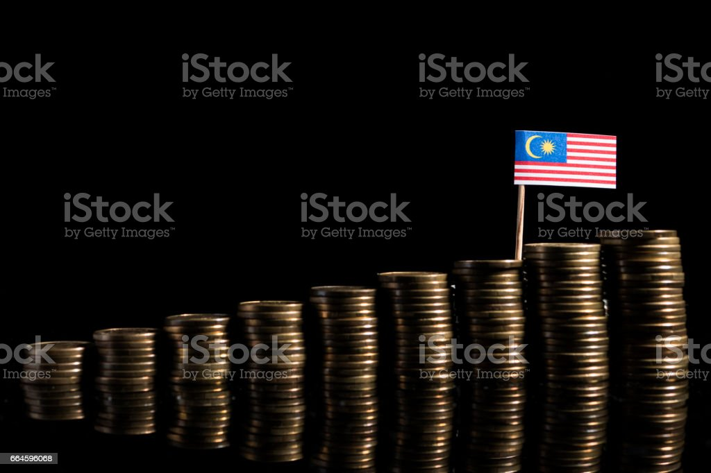 Malaysian flag with lot of coins isolated on black background stock photo