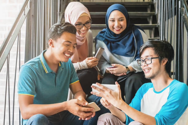 Malaysian friends watching video on mobile phone stock photo