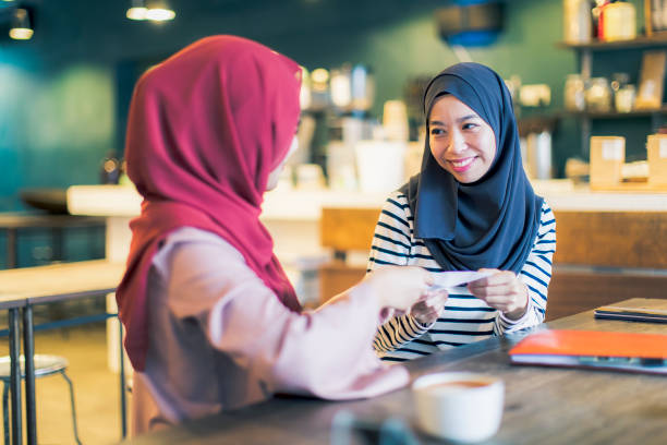 Malaysian Girls at a Cafe Exchanging an Envelope Malaysia, Kuala Lumpur, Positive Emotions, Contract, Business - Malaysian girl receiving her first cheque borrowing stock pictures, royalty-free photos & images