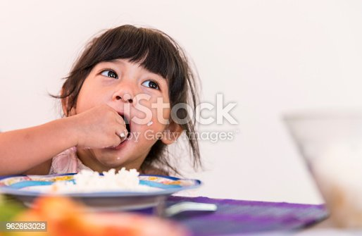 Young female child eating rice using her hand