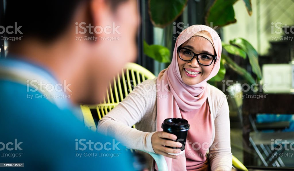 Malaysian man and woman sitting and talking royalty-free stock photo