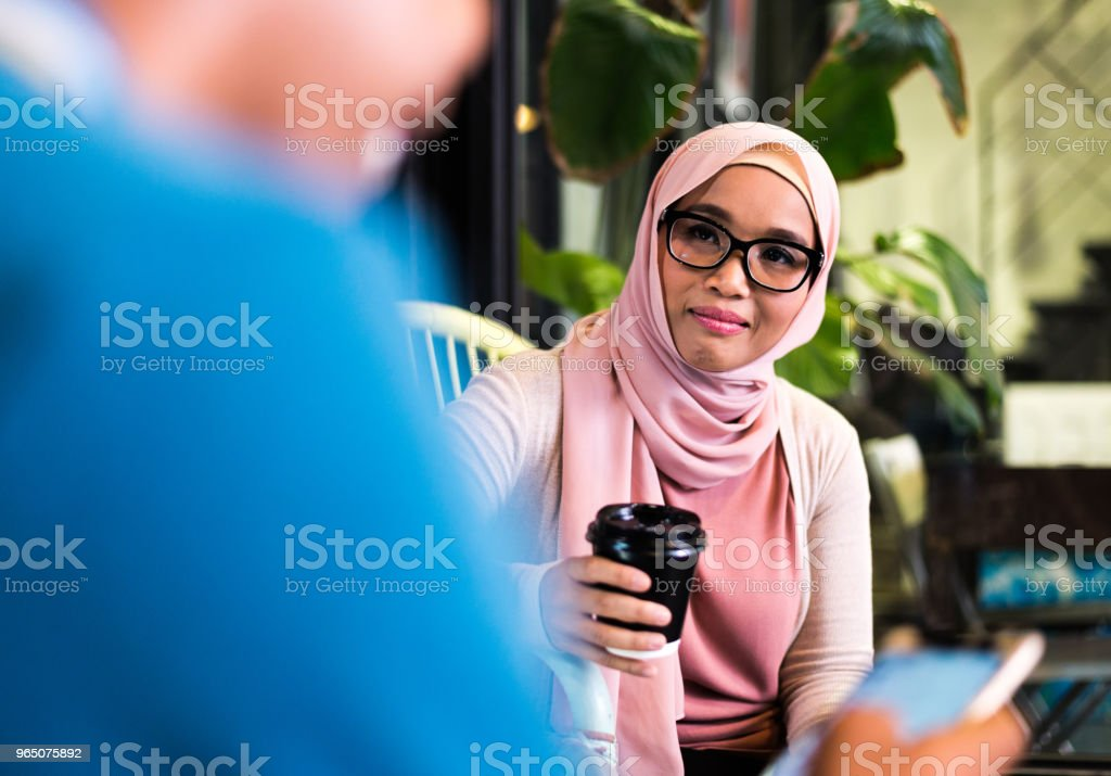 Malaysian man and woman sitting and talking zbiór zdjęć royalty-free