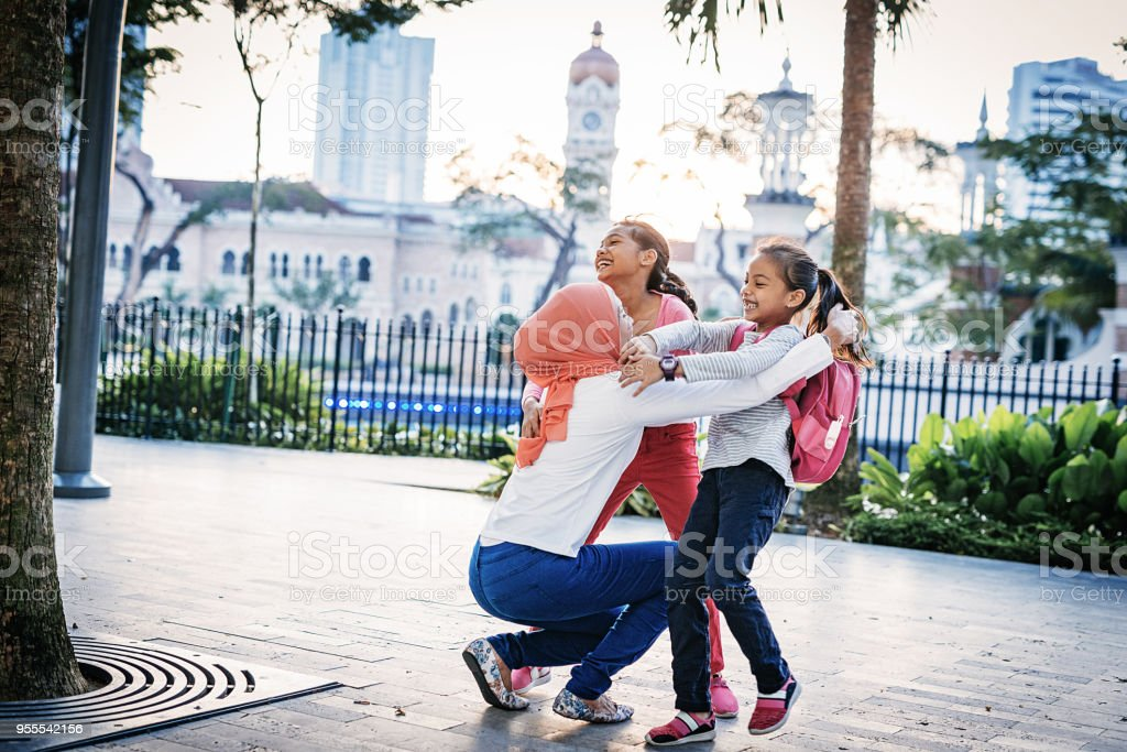 Malaysian Muslim mother with two daughters spending relaxing...