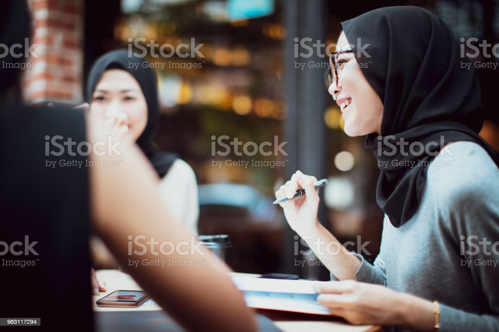Malaysian students having banter at a cafe stock photo