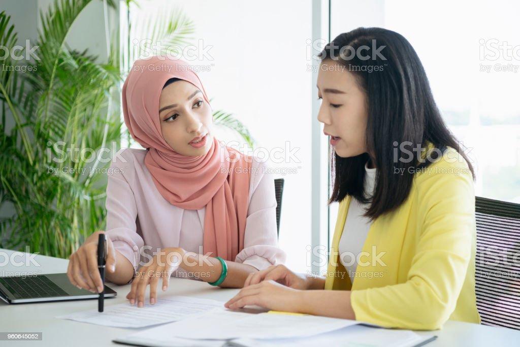 Malaysian woman explaining document stock photo