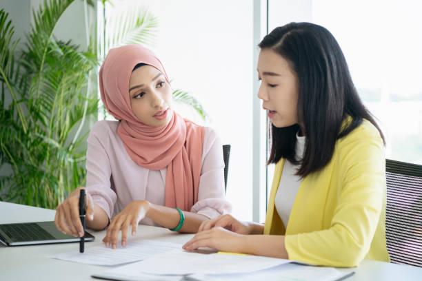 malaysian woman explaining document - хиджаб стоковые фото и изображения