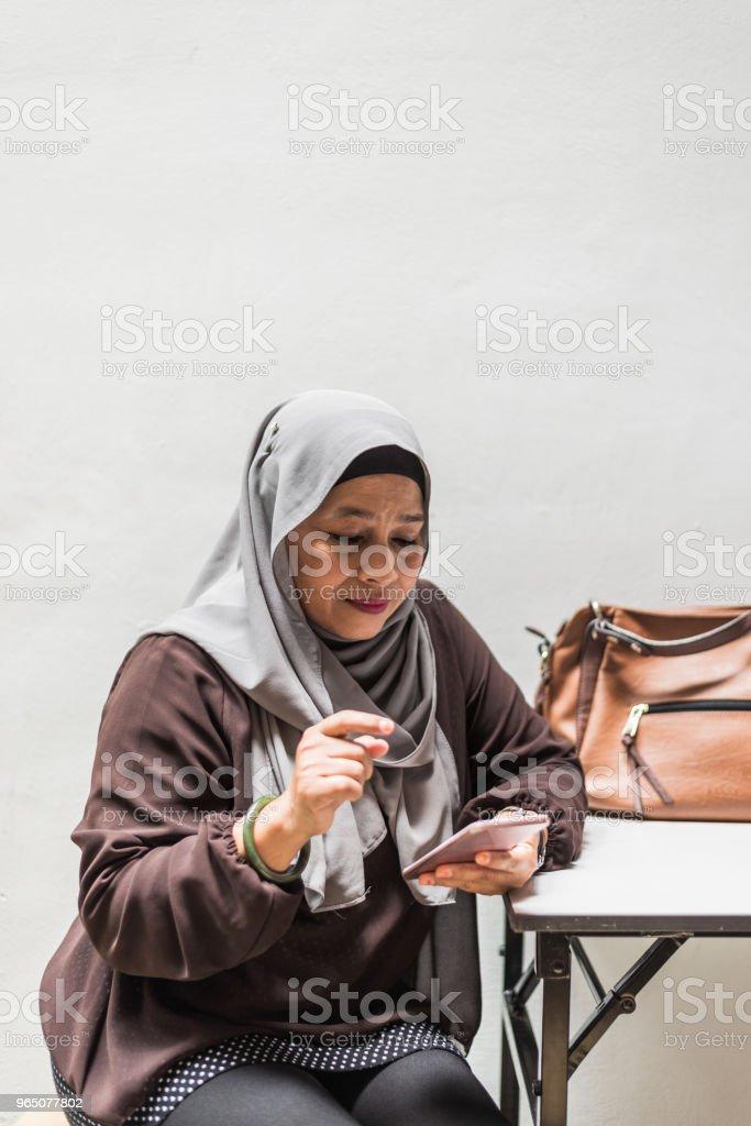 Malaysian woman having a break from work, texting on the phone zbiór zdjęć royalty-free