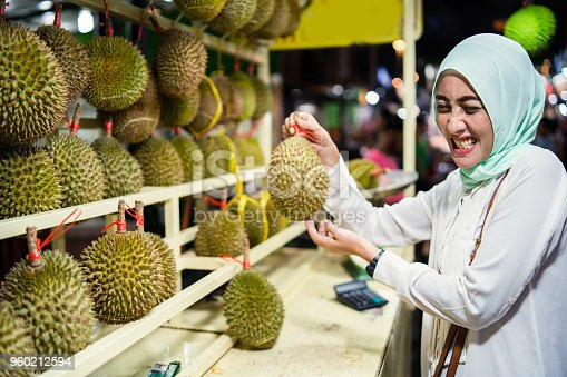 Malaysian woman holding Durian fruit known for its smell.