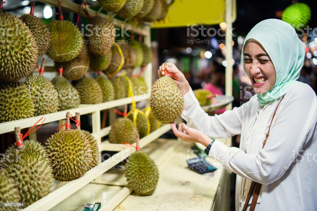 Malaysian woman holding Durian fruit known for its smell. stock photo