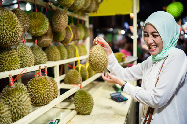 Malaysian woman holding Durian fruit known for its smell. Malaysian woman holding Durian fruit known for its smell. lahore pakistan stock pictures, royalty-free photos & images