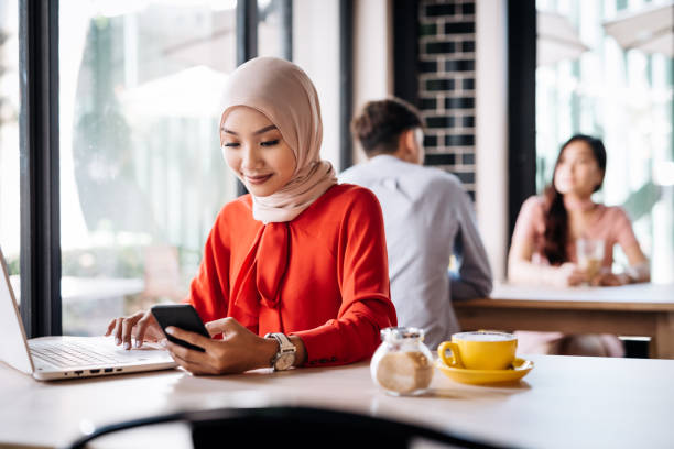Malaysian woman in cafe using electronic banking on laptop Malaysian woman with hijab sitting in cafe business Malaysia stock pictures, royalty-free photos & images