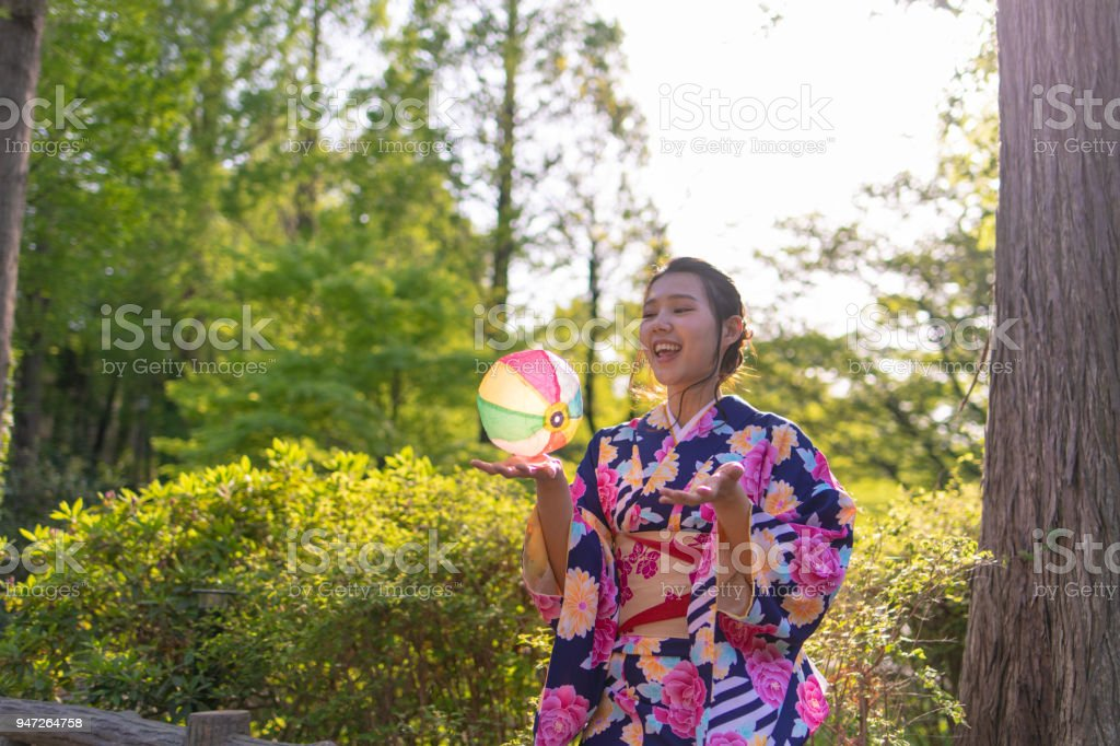 Malaysian woman in kimono playing with traditional Japanese paper baloon stock photo