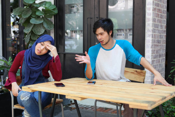 Malaysian Young Adults, Man and Woman Arguing Two Malaysian young adults, a Muslim woman in hijab and a man, arguing at a table. asian couple arguing stock pictures, royalty-free photos & images