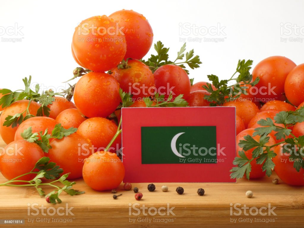 Maldives flag on a wooden panel with tomatoes isolated on a white background stock photo