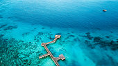 Maledives Island Jetty at turquoise lagoon with traditional Dhoni Boat anchored