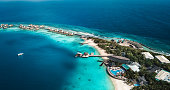 Maldives Island Resort Aerial with moon shaped reef from above.