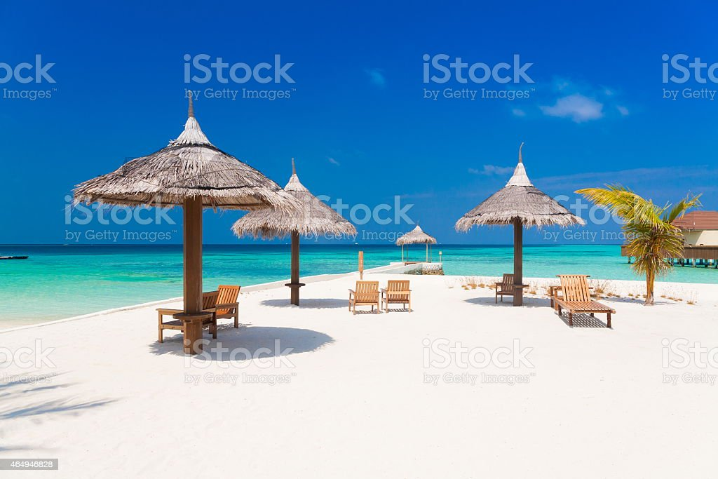 Maldives, white parasol and sunbed stock photo