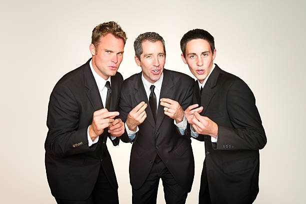 Male a capella trio in suits singing and snapping Male a capella trio in suits singing and snapping fingers in front of beige background. snapping stock pictures, royalty-free photos & images