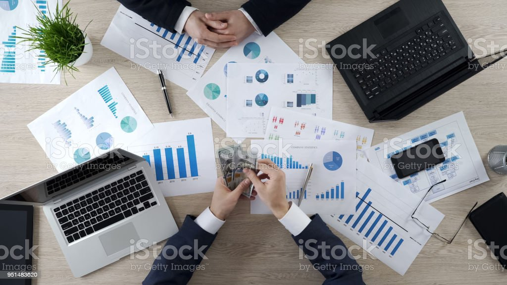 Male accountant counting cash, paying money to employee for accomplished project stock photo