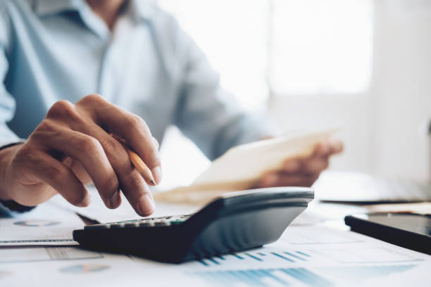 Male accountant or banker use calculator. Finances Saving Economy concept. Male accountant or banker use calculator. calculator stock pictures, royalty-free photos & images