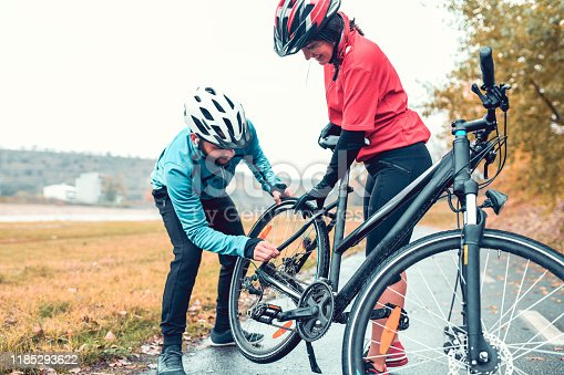 istock Male Adjusting Bike Gear For His Girlfriend 1185293622