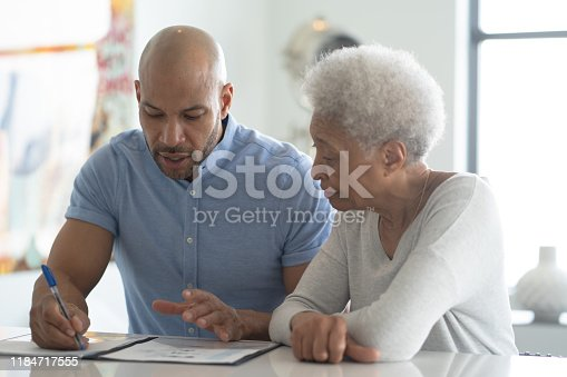 istock A Male African American Adviser Meets with A Female Senior Client stock photo 1184717555