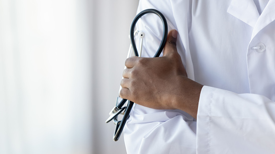 istock Male african doctor wear medical coat holding stethoscope, close up 1180549272