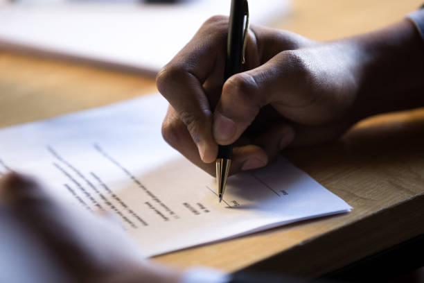 manliga afrikanska hand skriver signaturen rättsliga corporate pappersdokument - tillstånd bildbanksfoton och bilder