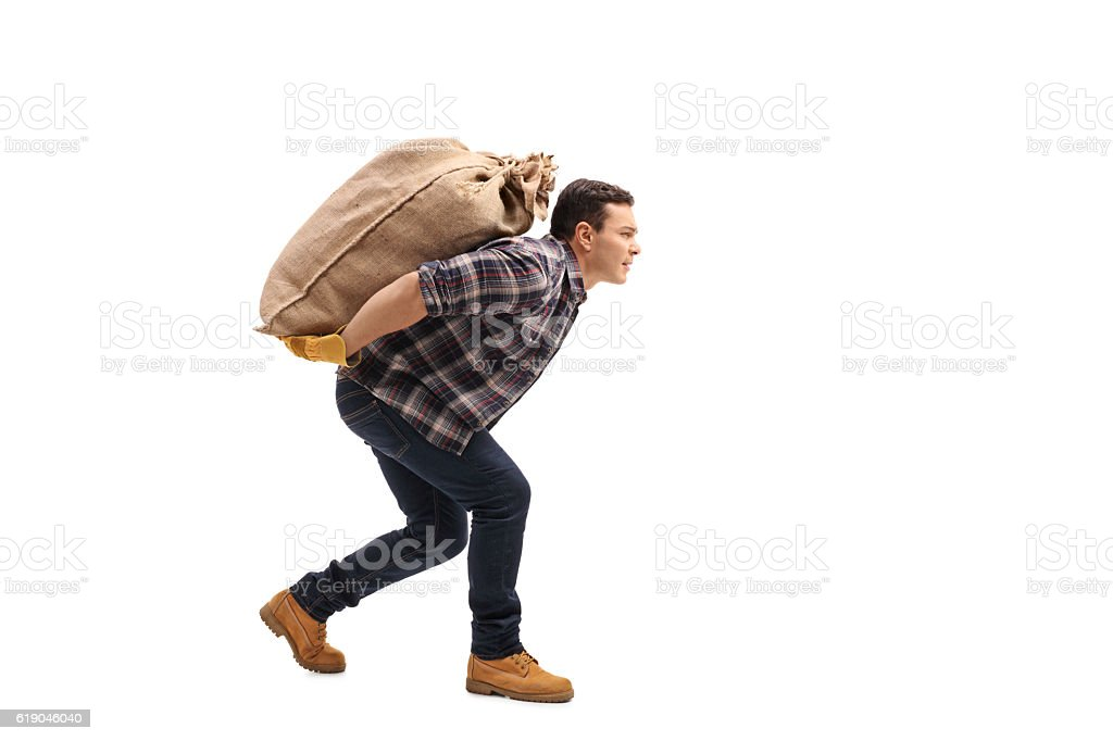 Male agricultural worker carrying burlap sack on his back stock photo