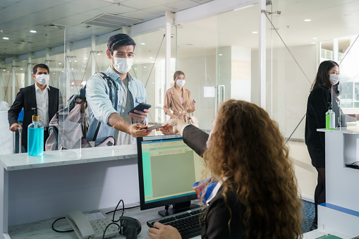A male airline passengerwith mask is handing over his passport at the airline counter check in through an acrylic barrier for disease prevention coronavirus or covid-19 at airport for New normal travel