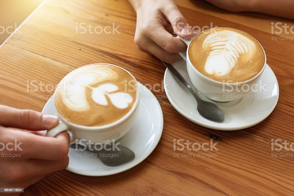 Hands holding coffee cups with designs in foam topping royalty-free stock photo