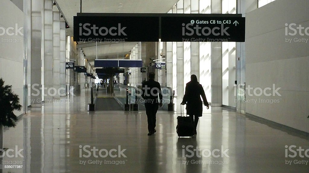 Male and Female Airline Travelers Walking In Airport stock photo