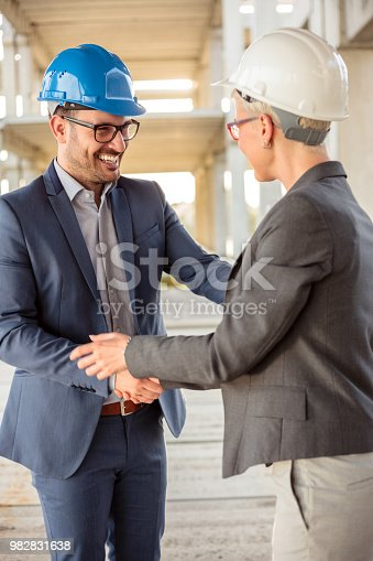 1129095769 istock photo Male and female architects or investors shaking hands after a successful meeting on a construction site 982831638